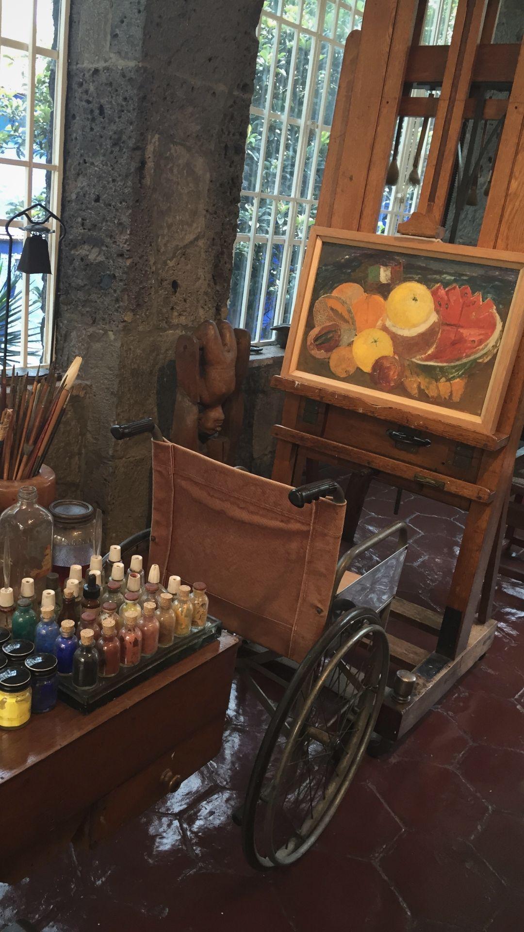 Cadeira de Rodas de Frida Kahlo em frente a uma pintura
