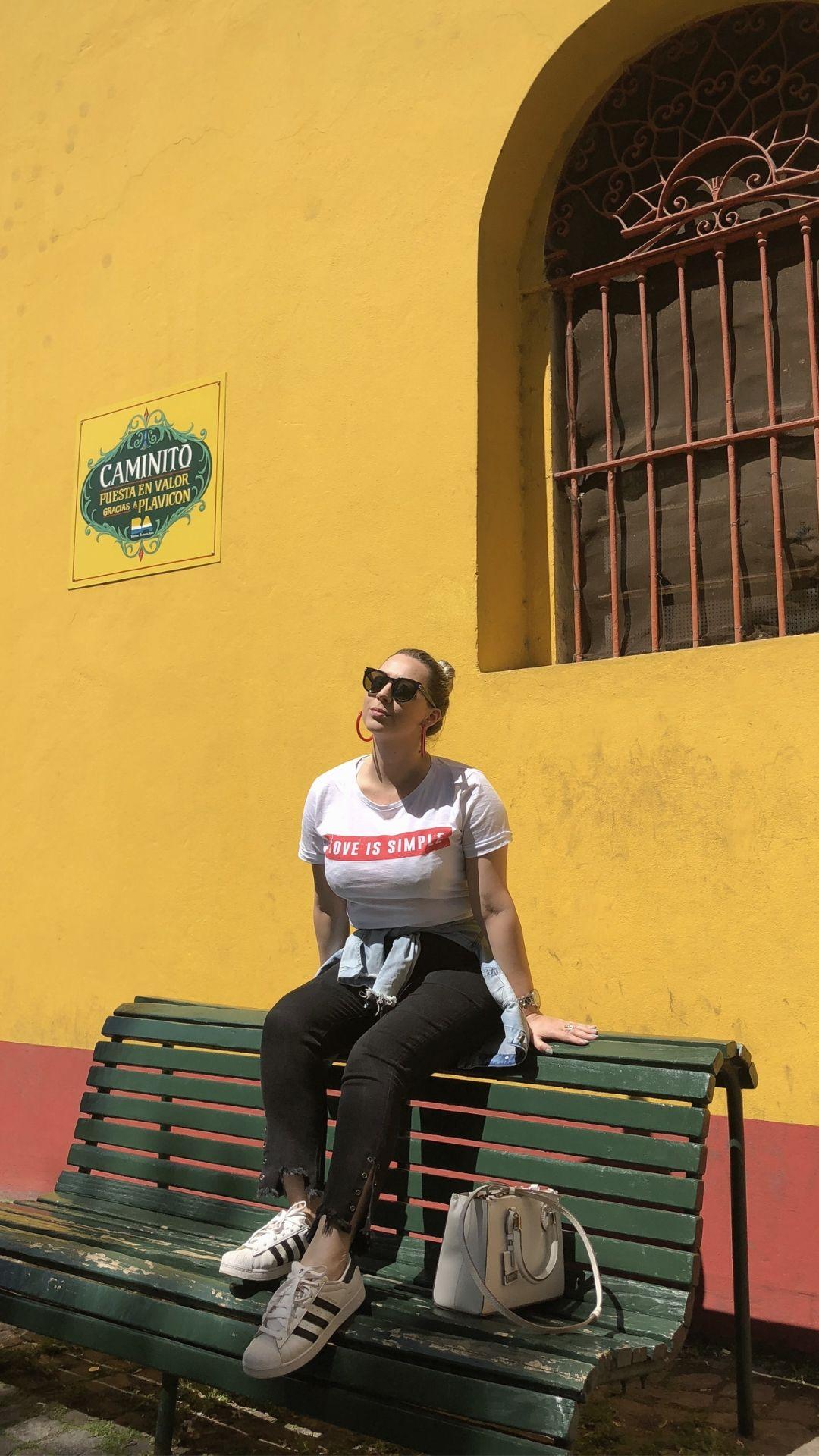 Fabi sentada em banco no bairro Caminito, Buenos Aires