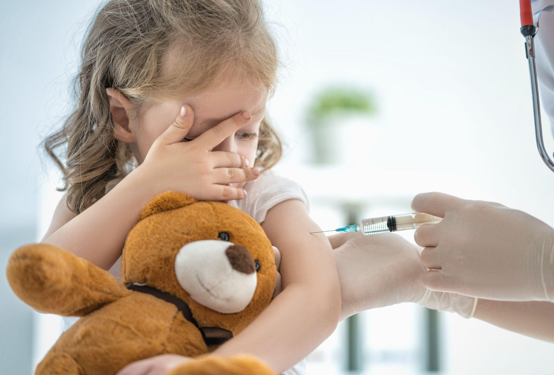 Criança segurança ursinho de pelúcia e tomando uma injeção
