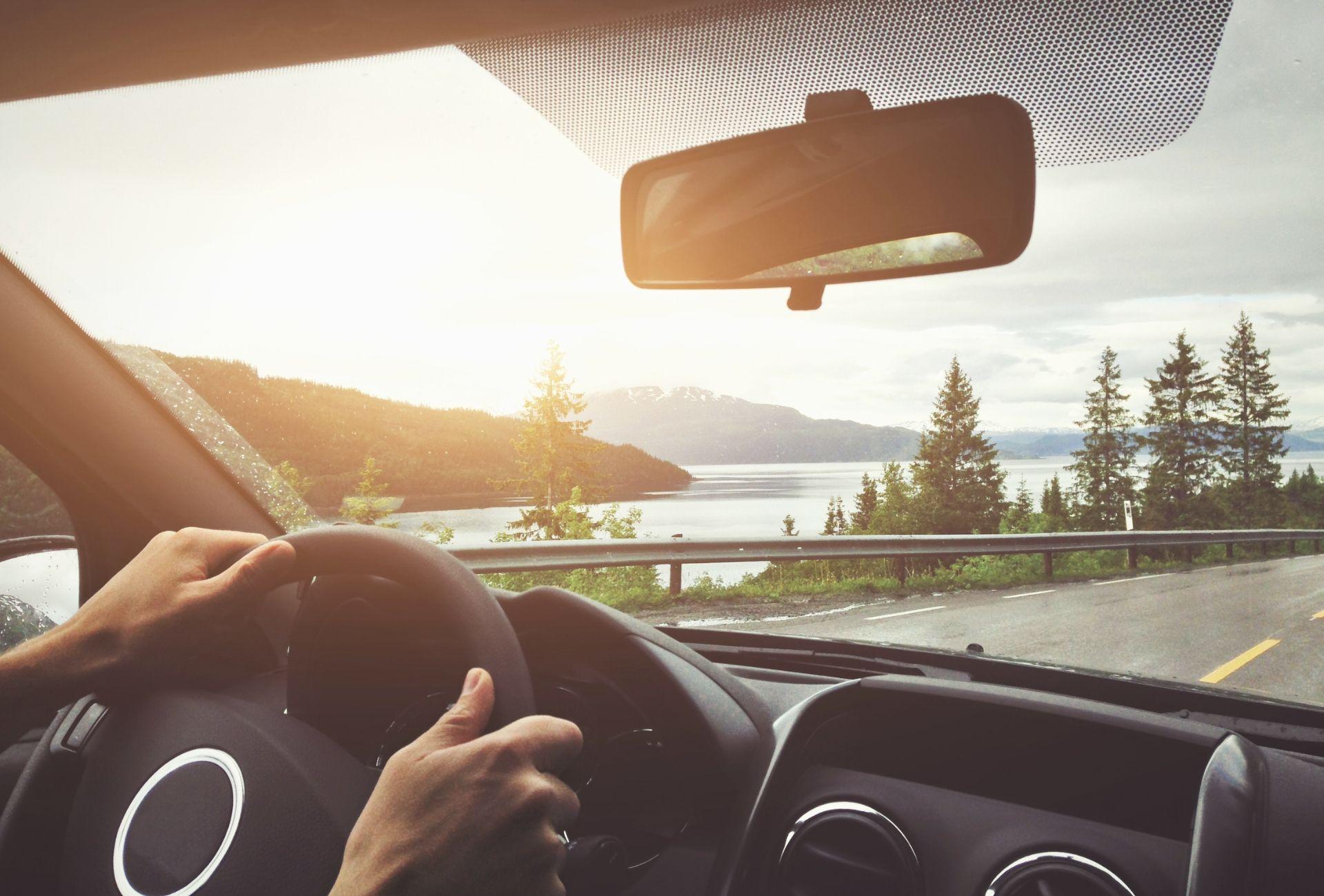 Pessoa dirigindo carro com paisagem ao fundo