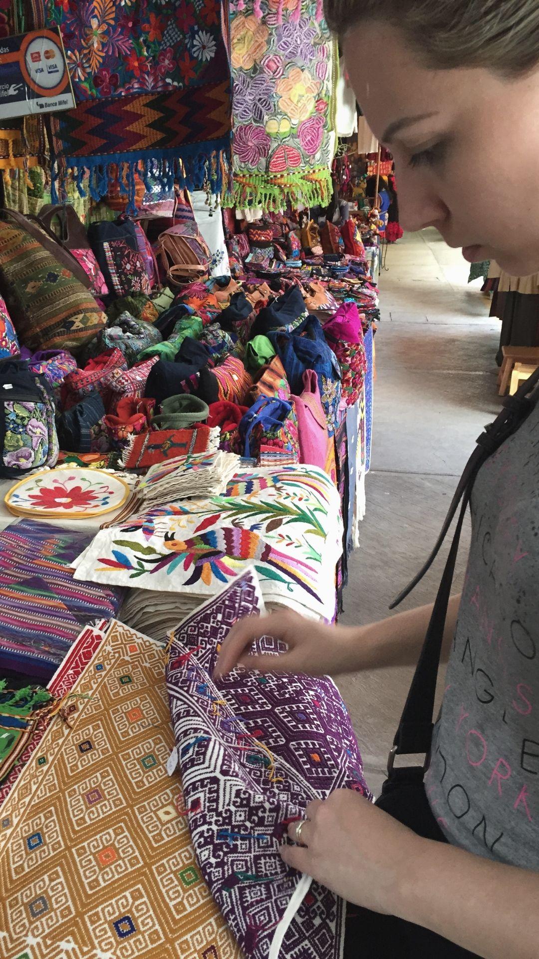 Fabi em uma feira de artesanato olhando toalhas