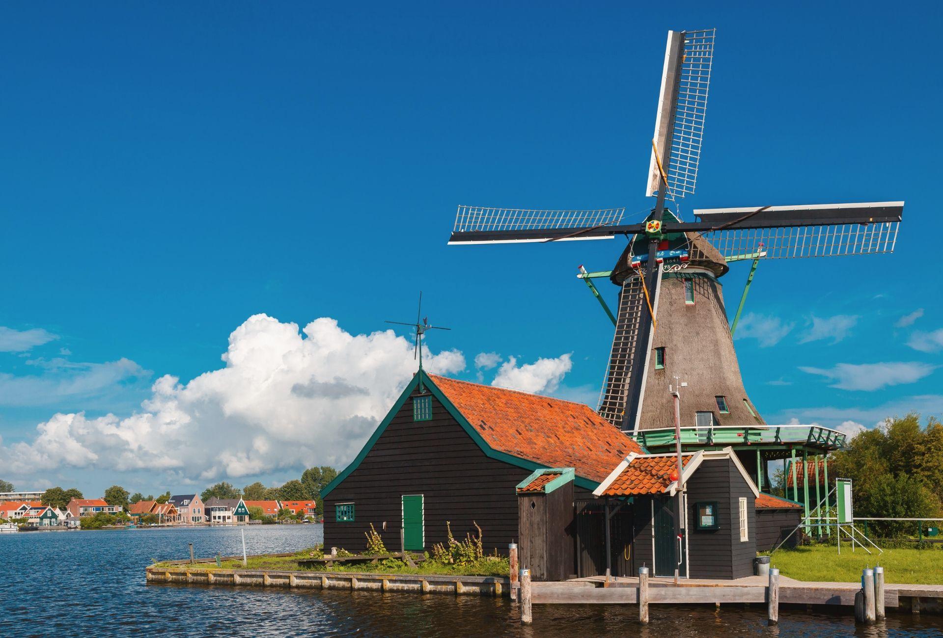 Moinho de vento ao lado de um lago em Zaanse Schans, na Holanda